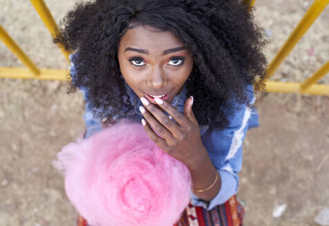View from above of a young black woman eating a cotton candy. Lubango, Angola. - VEGF00733