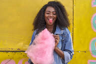 Portrait of smiling young woman with pink candyfloss sticking out tongue - VEGF00736
