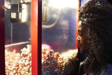 Young woman looking at popcorn in glass case at fair - VEGF00739