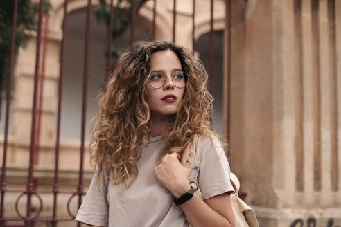 Beautiful young woman with curly hair and glasses in the city - LOTF00073