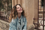 Happy young woman with curly hair and glasses in the city - LOTF00076