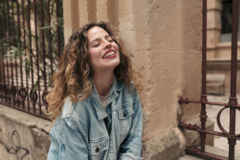 Beautiful teenager with blonde curly hair and blue eyes wearing a blue denim jacket and laughing. Palma de Mallorca, Balearic Islands, Spain. - LOTF00076