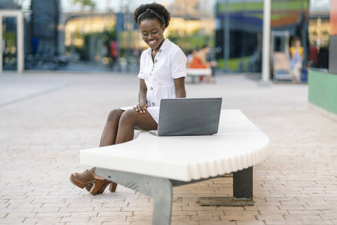Portrait of smiling young woman sitting on bench looking at laptop - DLTSF00189