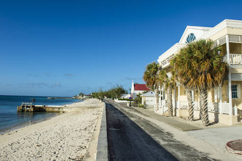 Colonial houses in front of beach against blue sky during sunny day at Cockburn town, Grand Turk - RUNF03226