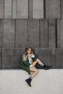 Portrait of blond young woman wearing green jacket sitting on a wall, Vienna, Austria - LHPF00956