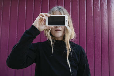 Portrait of blond young woman covering eyes with smartphone - LHPF00968