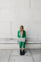 Blond young woman wearing green pantsuit sitting on a wall using laptop - LHPF00977