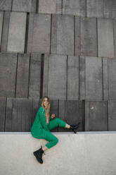 Blond young woman wearing green pantsuit sitting on a wall, Vienna, Austria - LHPF00980