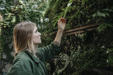 Young woman touching plants - LHPF00986