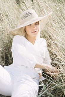 Portrait of blond young woman lying in beach dunes wearing white wrap blouse and summer hat - JESF00333
