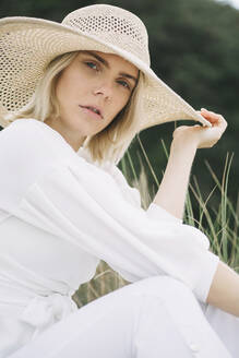Portrait of blond young woman sitting in dunes wearing white wrap blouse and summer hat - JESF00345