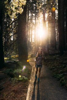 Woman with backpack hiking in the forest at sunset in Sequoia National Park, California, USA - GEMF03172