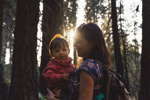 Mother holding a little girl in the forest at sunset in Sequoia National Park, California, USA - GEMF03175