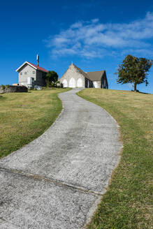 Diminishing perspective of footpath leading towards chapel against blue sky in Charlestown, Nevis - RUNF03246