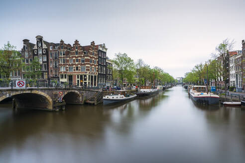 Netherlands, Amsterdam, Arch bridge over city canal with boats moored in background - XCF00227
