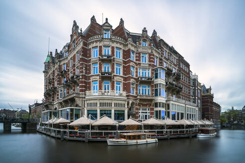 Netherlands, Amsterdam, Cafe canopies surrounding waterfront buildings - XCF00230