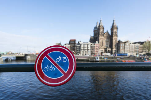 Netherlands, Amsterdam, No cycling sign hanging on railing withBasilica of Saint Nicholas in background - XCF00233