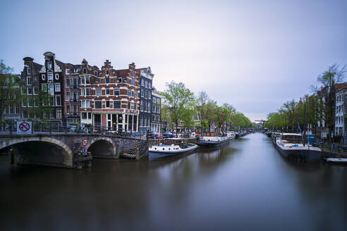 Netherlands, Amsterdam, Arch bridge over city canal with boats moored in background - XCF00236