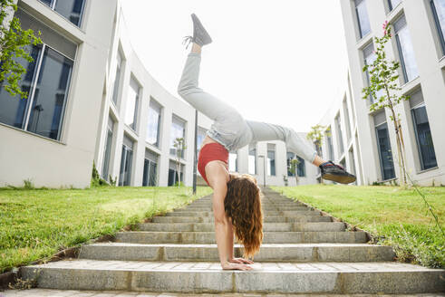Young woman doing a handstand on outdoor stairs - JSMF01272