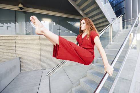 Sporty young woman doing acrobatics on a railing - JSMF01275