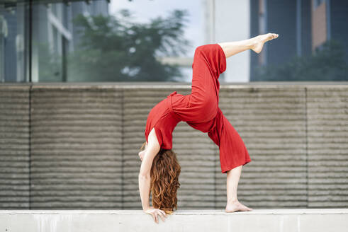Sporty young woman doing acrobatics on a concrete wall - JSMF01284