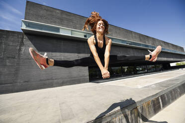 Happy sporty young woman jumping at a modern building - JSMF01290