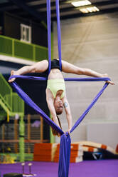 Young woman doing aerial silk in an exercise room - JSMF01299