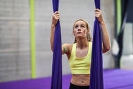 Young woman preparing for aerial silk in an exercise room - JSMF01302
