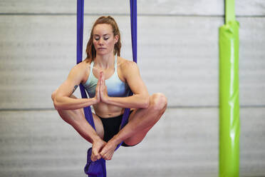 Young woman doing aerial silk in an exercise room - JSMF01311