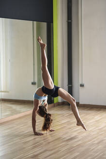Sporty young woman doing a handstand in exercise room - JSMF01314