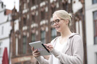 Portrait of young woman using tablet in the city - JESF00358