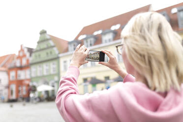 Portrait of blond woman photographing old houses with her smartphone - JESF00367