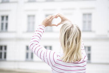 Rear view of young blond woman making heart shape with hands and fingers - JESF00379