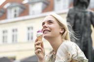 Portrait of young blond woman eating icecream - JESF00385