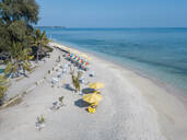 Drone view of chairs and colorful umbrellas arranged at Gili-Air Island against clear blue sky, Bali, Indonesia - KNTF03497