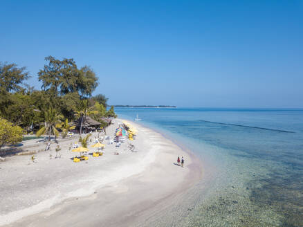 Drone view of Gili-Air Island against clear blue sky on sunny day, Bali, Indonesia - KNTF03500