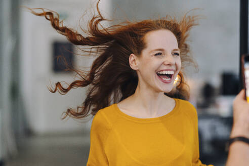 Laughing woman with windswept hair in office - KNSF06586