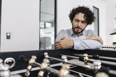 Businessman at foosball table in office - KNSF06592