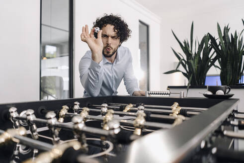Businessman with ball at foosball table in office - KNSF06595