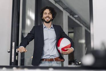 Happy businessman holding beach ball in office - KNSF06598