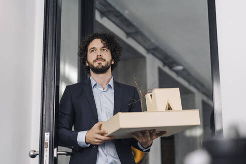 Architect in office holding architectural model - KNSF06601