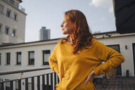 Redheaded woman standing on roof terrace - KNSF06616