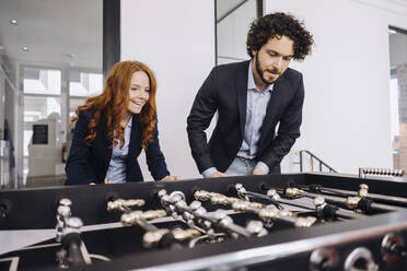 Businessman and businesswoman playing foosball in office - KNSF06622