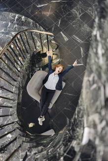 Top view of cheerful businesswoman sitting in armchair at staircase - KNSF06625
