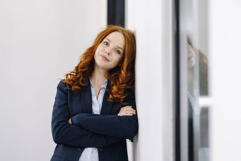 Portrait of redheaded businesswoman leaning against a wall - KNSF06631