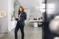 Portrait of redheaded businesswoman using laptop in office - KNSF06634