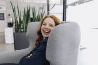 Happy redheaded businesswoman sitting in armchair - KNSF06637
