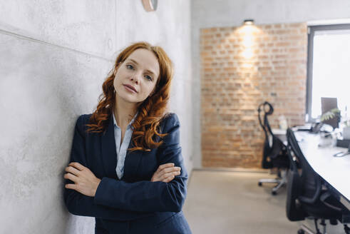 Portrait of confident redheaded businesswoman leaning against a wall in office - KNSF06640