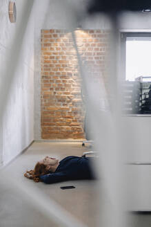 Tired businesswoman lying on the floor in office - KNSF06643