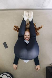 Businesswoman lying on the floor in office exercising - KNSF06646